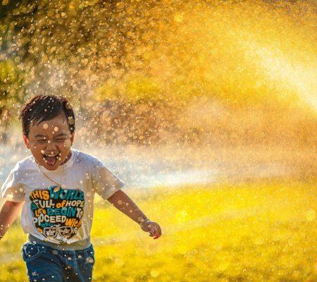 Boy playing in sprinkler at park